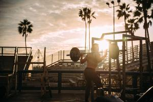 bodybuilder-exercising-sunset-84960562